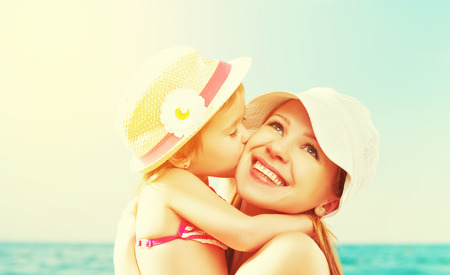 Photo for happy family on the beach. baby daughter kissing mother  at sea - Royalty Free Image