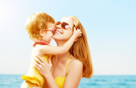 Photo pour happy family on the beach. baby daughter kissing mother  at sea - image libre de droit