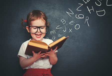 Photo for cute little girl with glasses reading a book with departing letters about Chalkboard - Royalty Free Image
