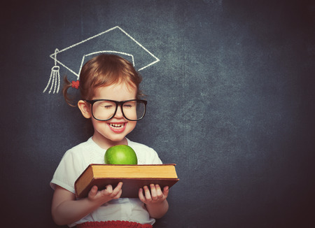 Photo pour pretty little girl schoolgirl with books and apple in a school board - image libre de droit