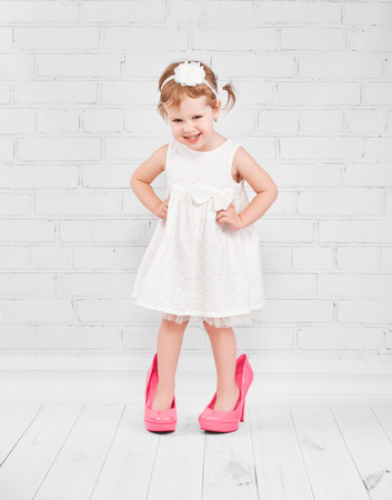 Photo for little girl fashionista in her mother's big pink heeled shoes - Royalty Free Image