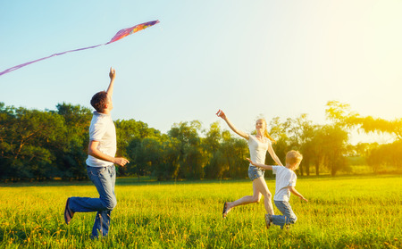 Foto de happy family in summer nature. Dad, mom and son child flying a kite - Imagen libre de derechos