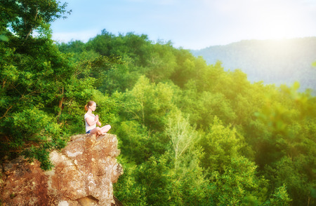 Photo for woman meditating in lotus posture, doing yoga on top of the mountain on a rock in nature in the forest - Royalty Free Image