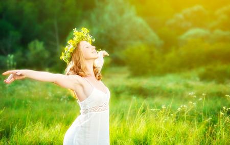 Foto de happy woman in wreath outdoors summer enjoying life opening hands - Imagen libre de derechos