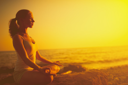 Photo pour yoga in the beach. woman meditating in lotus pose on the beach at sunset - image libre de droit