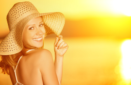 Photo for beauty happy smiling woman in a hat at sea at sunset on the beach - Royalty Free Image