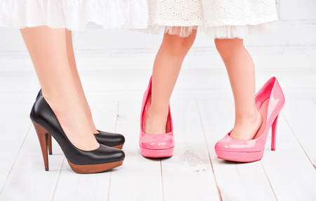 Foto de legs mother and daughter little girl fashionista in pink shoes on high heels - Imagen libre de derechos