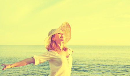 Photo pour Happy beauty woman in a hat opened his hands, relaxes and enjoys the sunset over the sea on the beach - image libre de droit