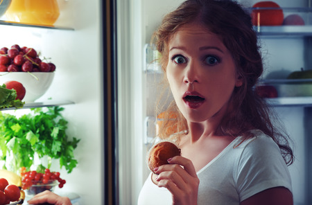 Photo pour woman eats sweets at night to sneak in a refrigerator - image libre de droit