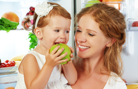 Photo pour happy family mother and child baby daughter around the refrigerator with healthy food fruits and vegetables - image libre de droit