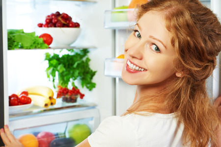 Photo pour Happy woman standing at the open refrigerator with fruits, vegetables and healthy food - image libre de droit