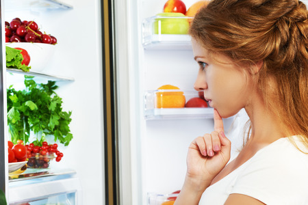 Foto per Happy woman standing at the open refrigerator with fruits, vegetables and healthy food - Immagine Royalty Free