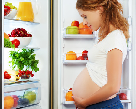 Photo for nutrition and diet during pregnancy. Pregnant woman standing near refrigerator with fruits and vegetables - Royalty Free Image