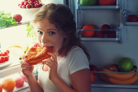 Foto de woman eats sweets at night to sneak in a refrigerator - Imagen libre de derechos