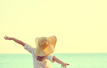 Photo pour Happy beauty woman in hat is back opened his hands, relaxes and enjoys the sunset over the sea on the beach - image libre de droit