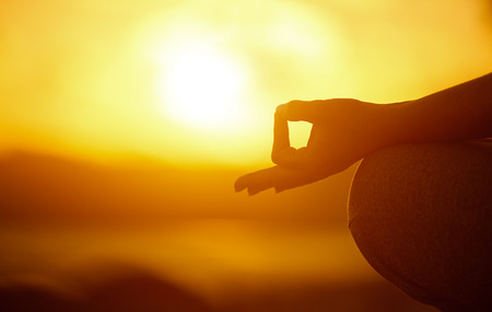Photo pour Yoga concept. hand woman practicing lotus pose on the beach at sunset - image libre de droit