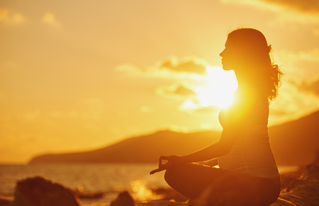 Foto de Pregnant woman practicing yoga, sitting in lotus position on a beach at sunset - Imagen libre de derechos