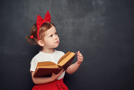 Photo pour funny happy little girl schoolgirl with a book from the blackboard - image libre de droit