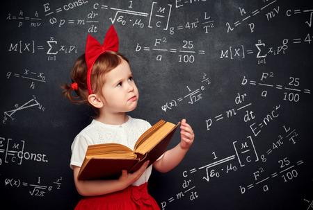 Foto de wunderkind little girl schoolgirl with a book from the blackboard with physical formulas - Imagen libre de derechos