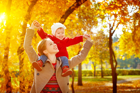 Foto de happy family: mother and child little daughter play cuddling on autumn walk in nature outdoors - Imagen libre de derechos