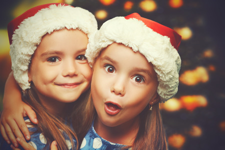 Foto de Christmas Happy funny children twins sisters hugging - Imagen libre de derechos