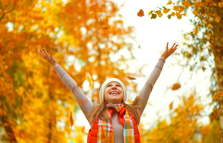 Photo pour Happy girl throws up autumn leaves in the park for a walk outdoors - image libre de droit