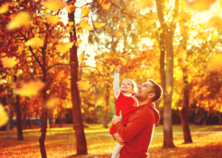 Foto de Happy family father and child daughter on a walk in the autumn leaf fall in park - Imagen libre de derechos