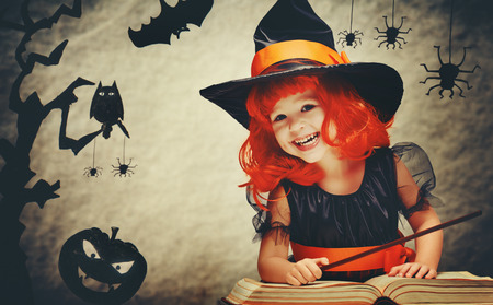 Photo for Halloween. cheerful little witch with a magic wand and the book conjure and laughs. - Royalty Free Image