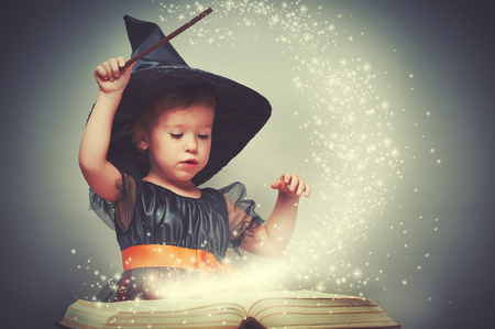 Photo for Halloween. cheerful little witch with a magic wand and glowing book conjure and laughs. - Royalty Free Image
