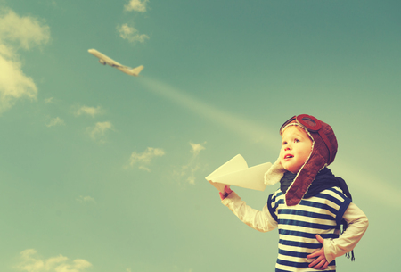 Photo for Happy child dreams of becoming a pilot aviator and plays with planes in the sky - Royalty Free Image