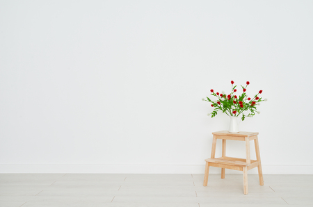 Foto de concept of a bouquet of flowers on a stepladder on the background white brick wall in an empty room - Imagen libre de derechos