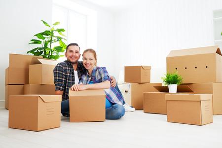 Foto de moving to a new apartment. Happy family couple and a lot of cardboard boxes. - Imagen libre de derechos