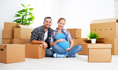 Photo for moving to a new apartment. young family pregnant wife and husband with cardboard boxes - Royalty Free Image