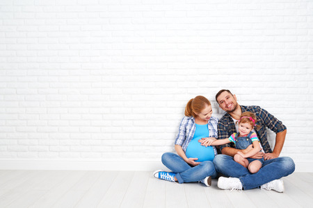 Photo pour Happy family father and pregnant mother and child daughter near a blank brick wall in the room - image libre de droit