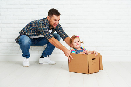 Foto per happy family moves to new apartment. dad and child  daughter playing  and have fun packs in cardboard boxes - Immagine Royalty Free