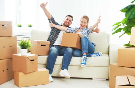 Foto de moving to a new apartment. Happy family couple and a lot of cardboard boxes. - Imagen libre de derechos