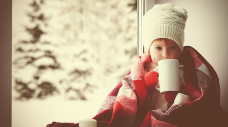 Foto de child little girl sitting by the window with a cup of hot tea and looking at the winter forest - Imagen libre de derechos