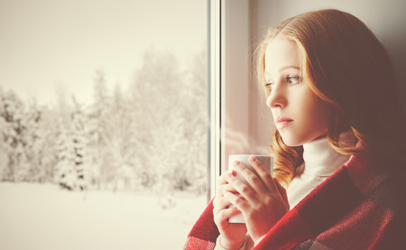 Foto de Pensive sad girl with a warming drink looking out the window in the winter forest - Imagen libre de derechos