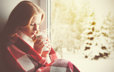 Foto de Pensive sad girl with a warming drink looking out the window in the winter forest - Imagen libre de derechos