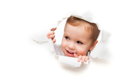 Foto de Funny child  baby girl  peeping through a hole in an empty white paper poster - Imagen libre de derechos