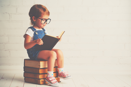 Foto de happy child little girl with glasses reading a books - Imagen libre de derechos