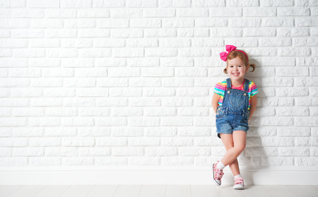 Photo pour Happy child little girl laughing at a blank empty brick wall - image libre de droit