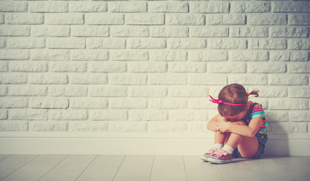 Photo pour little child girl crying and sad about an empty brick wall - image libre de droit