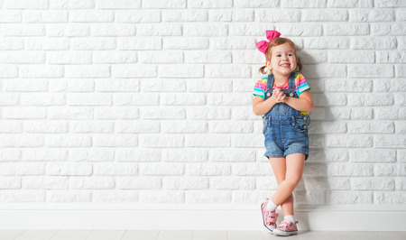 Photo for Happy child little girl laughing at a blank empty brick wall - Royalty Free Image