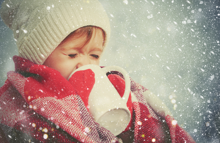 Photo for happy child girl with a cup of hot drink on a cold winter outdoors - Royalty Free Image