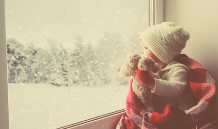 Photo for child little girl sitting by the window with a teddy bear and looking at the winter forest - Royalty Free Image