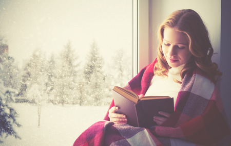 Photo pour happy girl reading a book by the window in the winter - image libre de droit