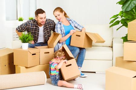 Foto de moving to a new home. Happy family with cardboard boxes - Imagen libre de derechos