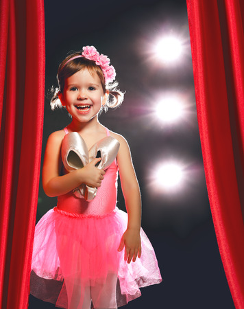 Photo for little child girl ballerina ballet dancer on the stage in red side scenes - Royalty Free Image