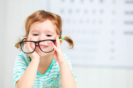 Photo for concept vision testing. child  girl with eyeglasses at the doctor ophthalmologist - Royalty Free Image